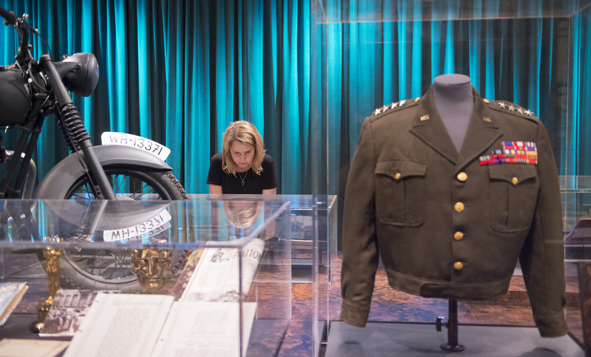 "Exhibition View of ""Real to Reel: A Century of War Movies"". (LEFT) Replica motorbike from The Great Escape, Object: IWM (RIGHT) Patton costume worn by George C. Scott, Courtesy of Angels Costumes Photographed 28th June, 2016."