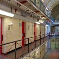 One of three long corridors running of a central hallway in Reading Prison. Pictured on the left is a painting of Wilde by Marlene Dumas. Image: James Lingwood, courtesy of Artangel