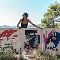 Rozalina Burkova with her finished paintings - titled Breathe, Swim and Dance - on Obonjan island