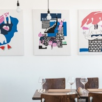 Rozalina Burkova's canvases on display in Obonjan restaurant The Kitchen. Burkova spent two weeks on the island as its first artist-in-residence. Images feature a woman swimming, people dancing late at night and someone meditating