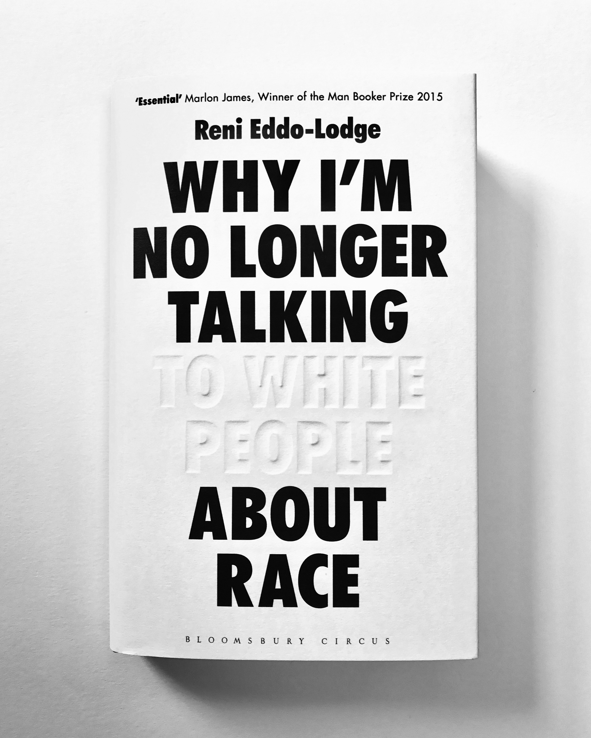 The black-and-white cover for Reni Enno-Lodge's book Why I'm No Longer Talking to White People About Race features blind debossed lettering