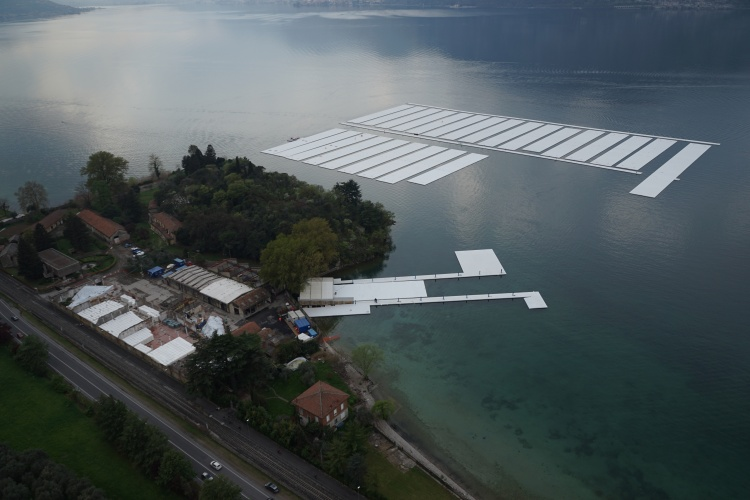 The Floating Piers - Aerial view of the project's building yard on the Montecolino peninsula (left) and the parking area for the thirty 100 by 16 meter sections on Lake Iseo (right), April 2016