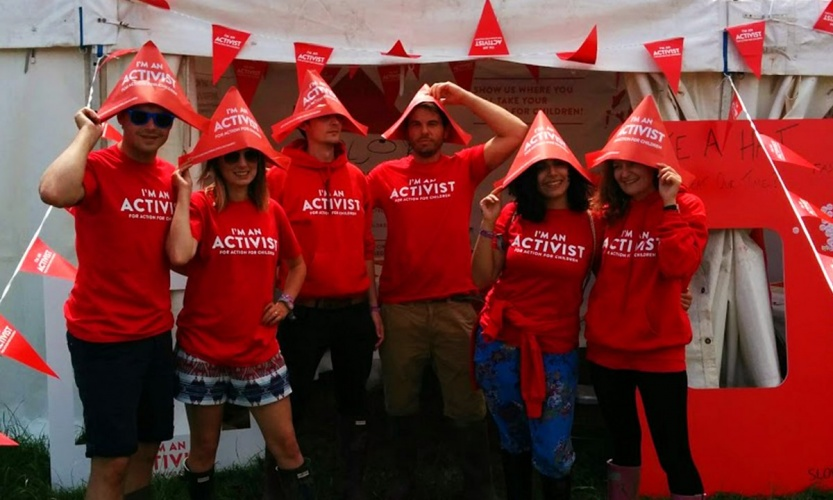 10 - I'm-an-Activist-for-Action-for-Children-promotional-staff-with-stand-next-to-Glastonbury-pyramid-stage-by-Neon-1200x720