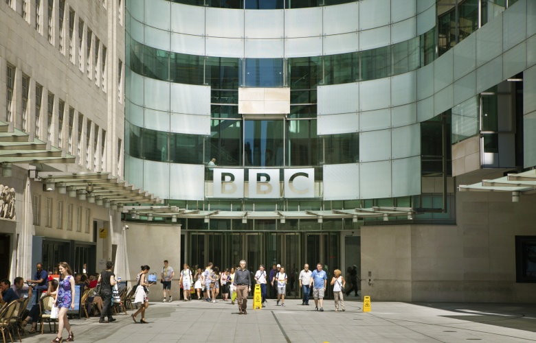 London, UK - July 3, 2014: BBC head office and square in front of main entrance with walking people