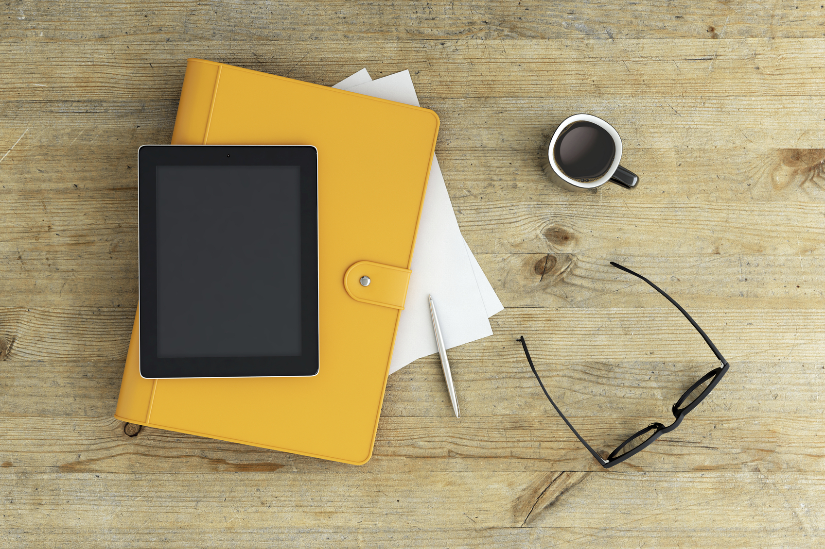 View from above on a working desk setup, bright yellow notebook, notes, coffee and glasses