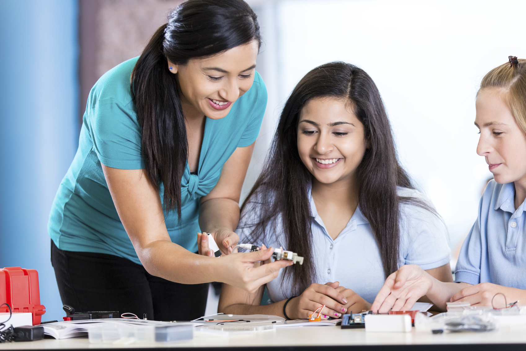 Mid adult Hispanic woman is teaching middle school or junior high school class about audio engineering. Teacher is using electronic or robotic parts to help students create speakers. Preteen Indian and Caucasian girls are smiling while studying STEM. Science, Technology, Engineering, and Math are focus of private school class.