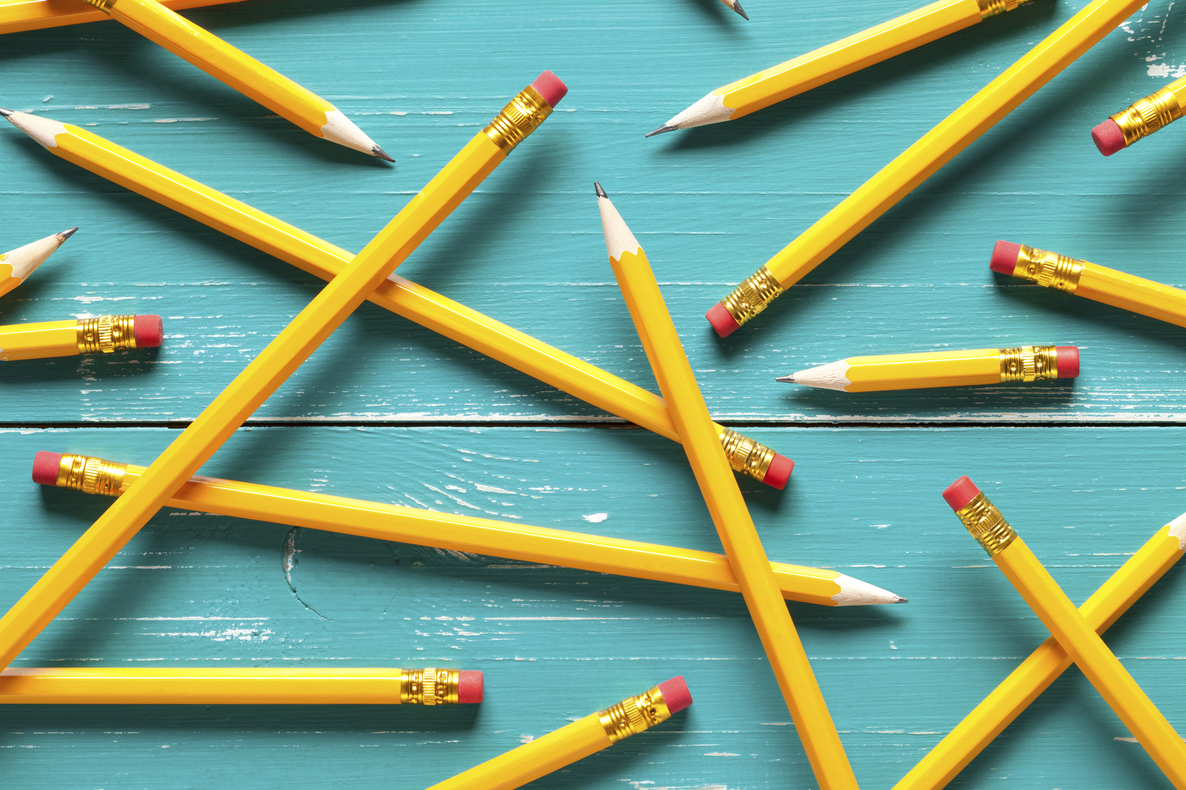 Close up of classic yellow pencils on turquoise table. This file is cleaned and retouched.