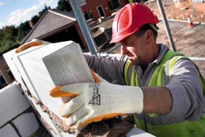 Builder building a wall using concrete blockwork