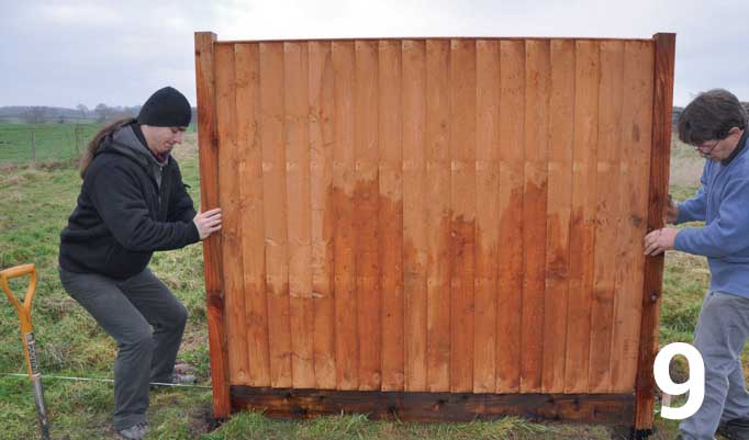 Lift the fence panel into position