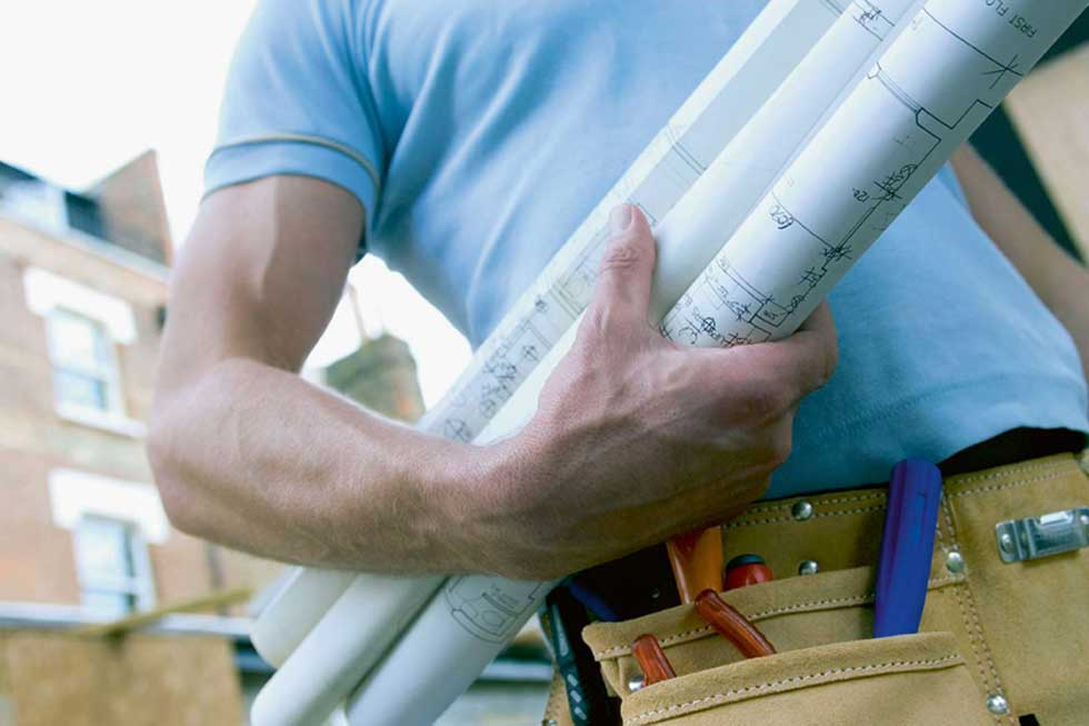 Building project blue prints under mans arm