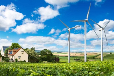 homes with renewable technology and solar panels built next to wind turbines