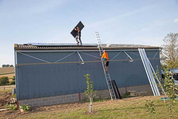 Two engineers installing photovoltaic solar PV panels on roof of steel barn Cotswolds UK