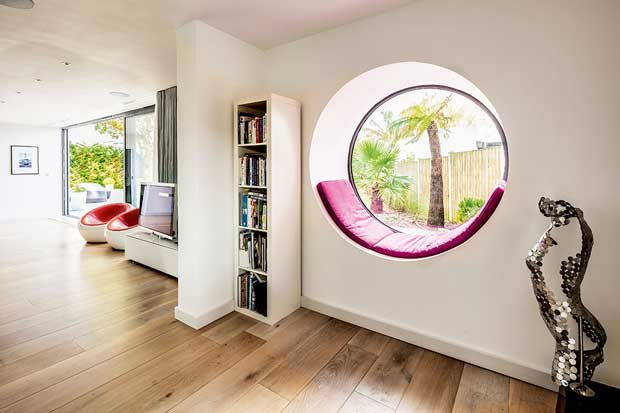 Circular window in a Bauhaus style home with white walls