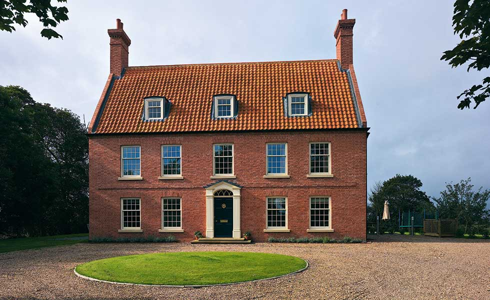 Neil Dowlman Architecture – This Georgian-style brick façade hides a 19th-century cottage behind its walls