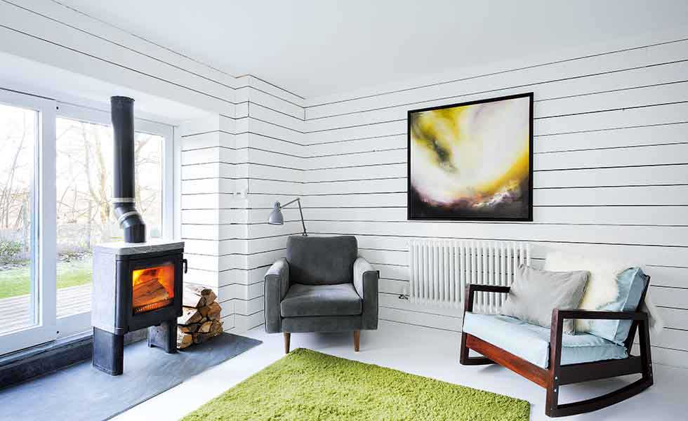 scandinavian style living room with white panelled walls in a stone cottage
