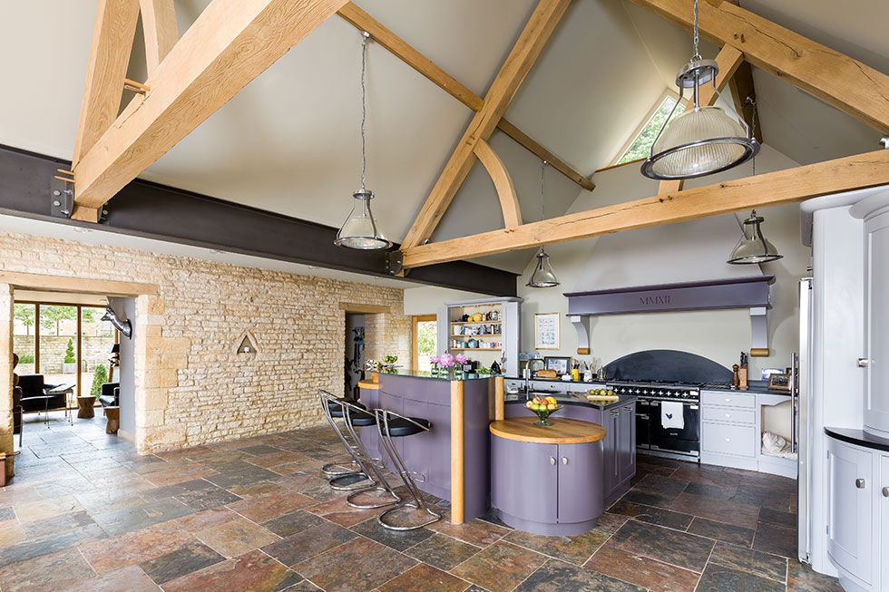The kitchen features striking purple units to add colour to the stone barn conversion