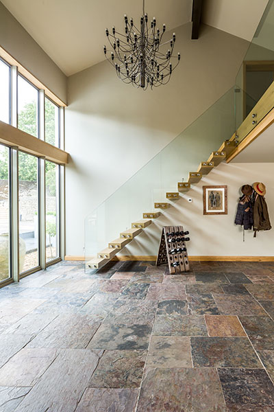 A contemporary glass and timber staircase with galleried landing above