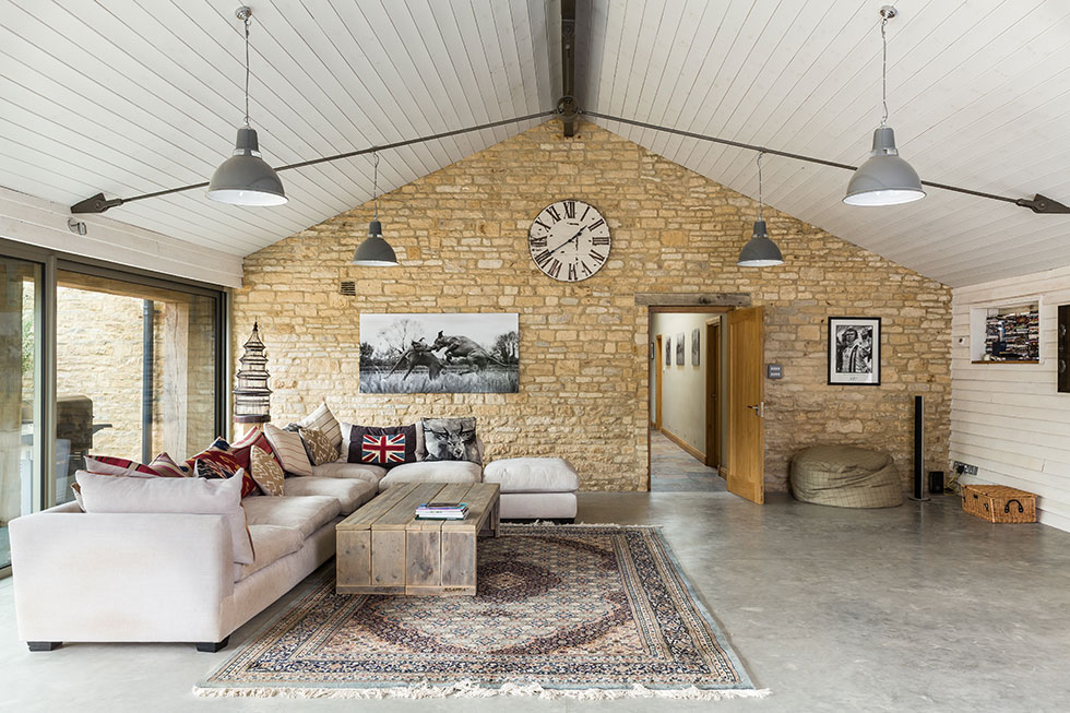 Sitting area within the renovated Cotswold stone barn conversion complete with exposed stone walls