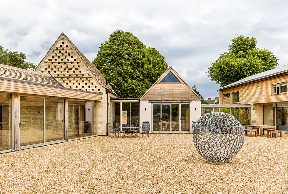 Cotswold stone barn with pebbled courtyard