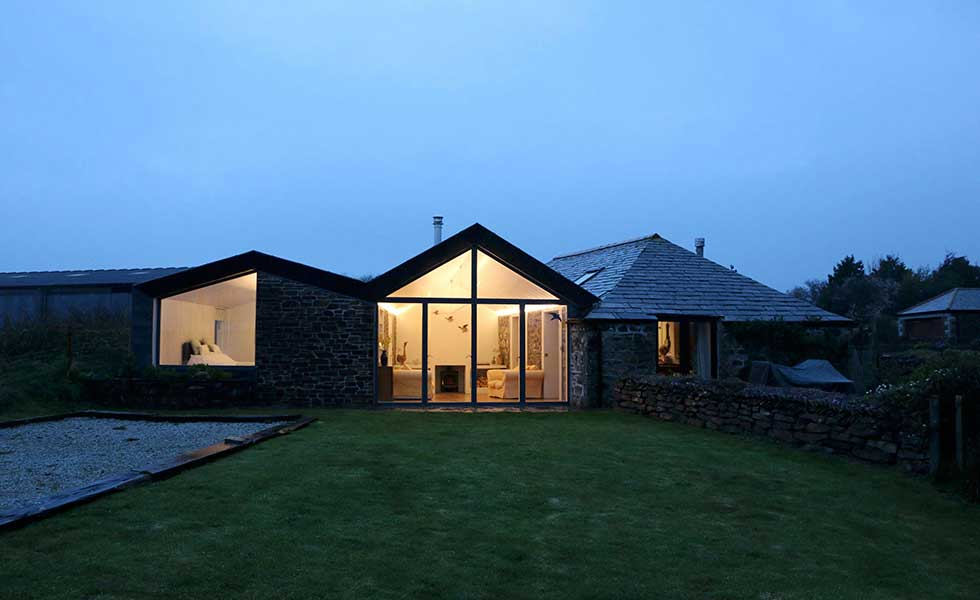 evening shot of stone cottage with glass front