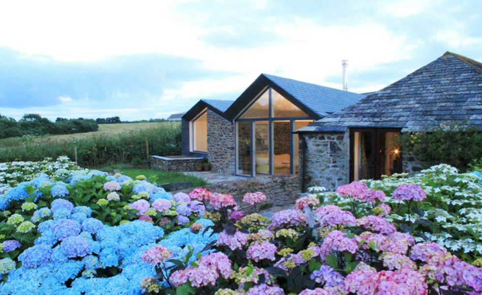 stone cottage with glass front and floral garden