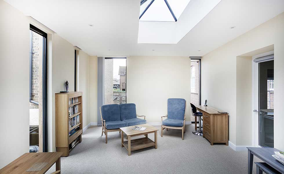 white living space with large skylight and blue furniture