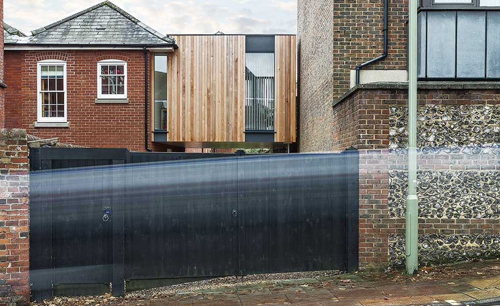 modern wooden panelled and glass extension behind black gate
