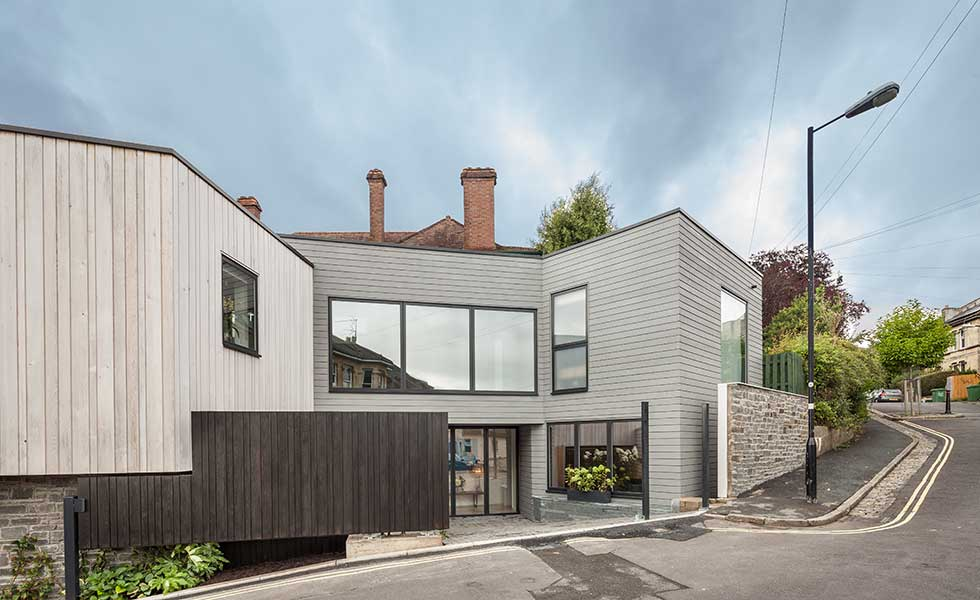 modern grey wooden panelled home with opening gate