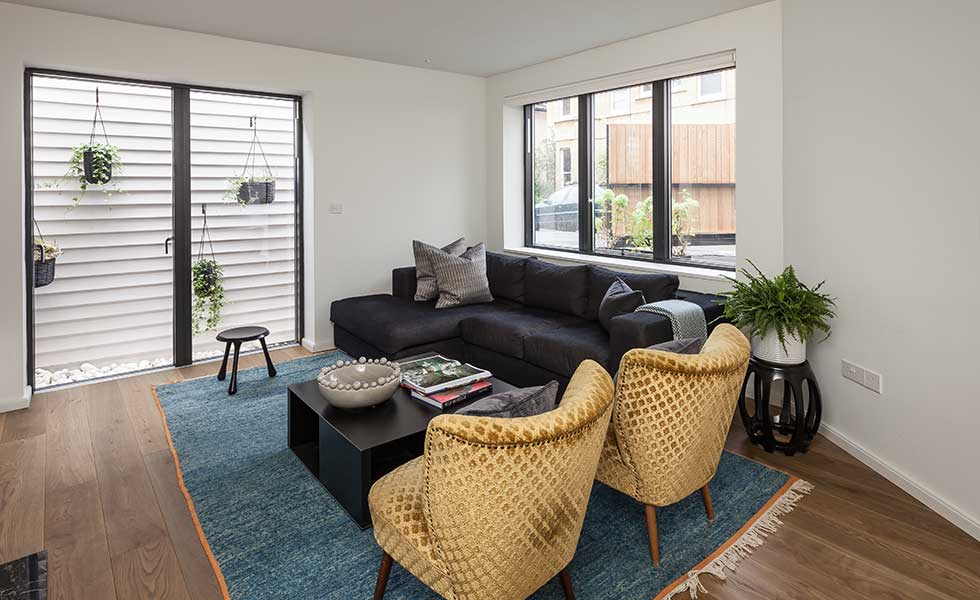 living space with blue rug and statement yellow chairs