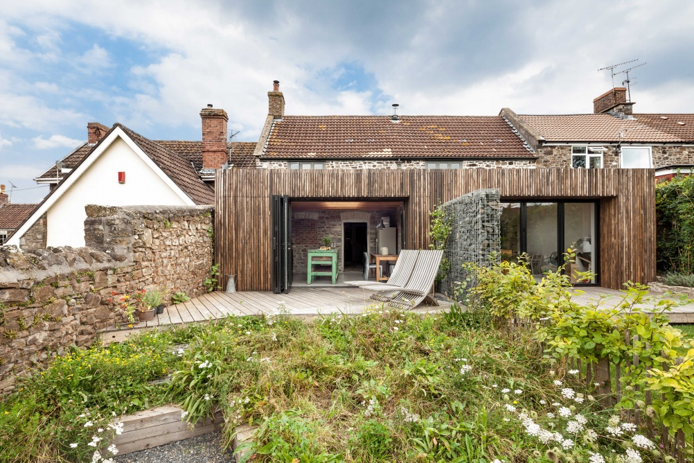 back garden of converted cottages with modern wooden panelled extension