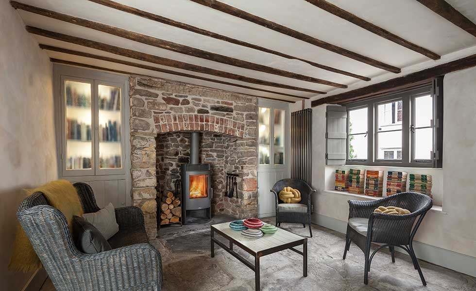 traditional cottage living space with exposed brick wall and wooden beams and log burner