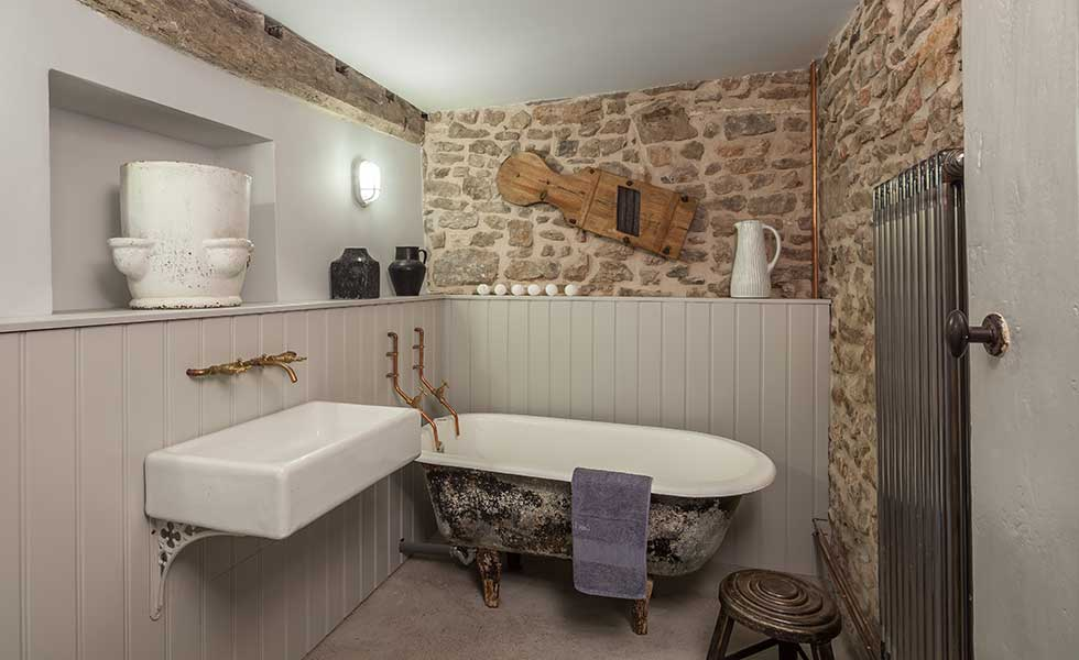 exposed stone wall bathroom in traditional cottage bathroom