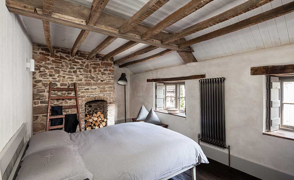 exposed brick wall bedroom in traditional cottage
