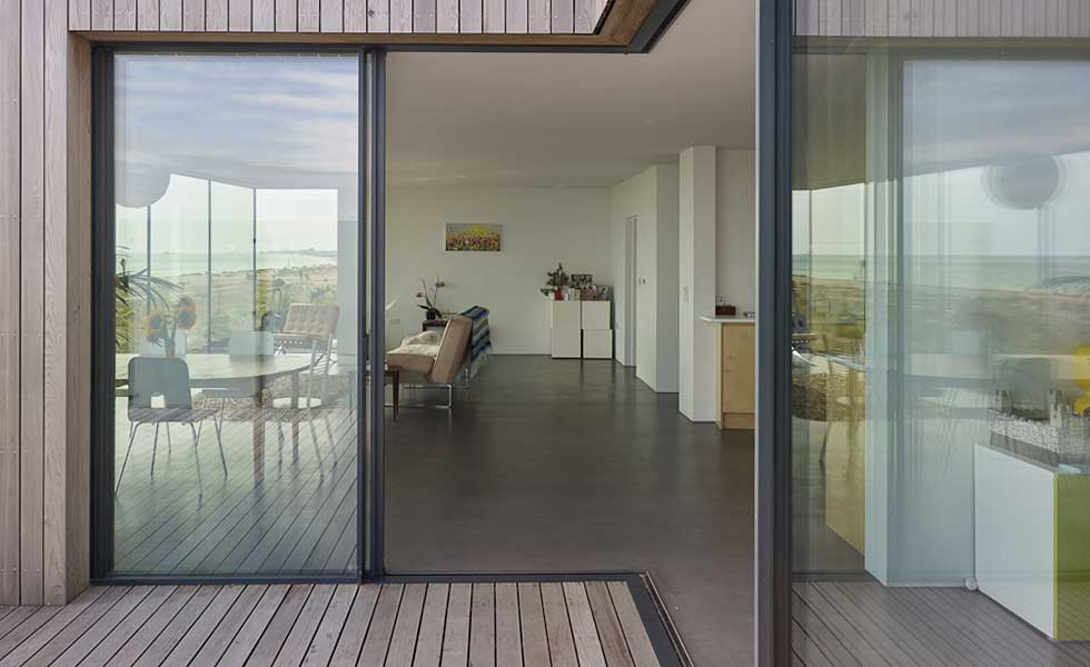 patio shot of modern glass and wooden panelled beachhouse