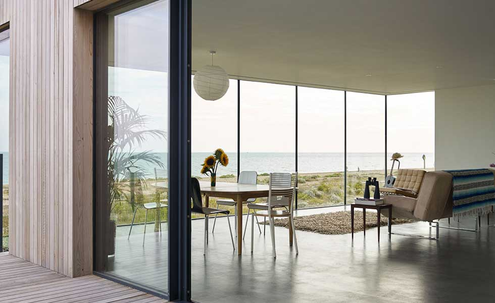 view through glass of modern beachfront house with open plan layout