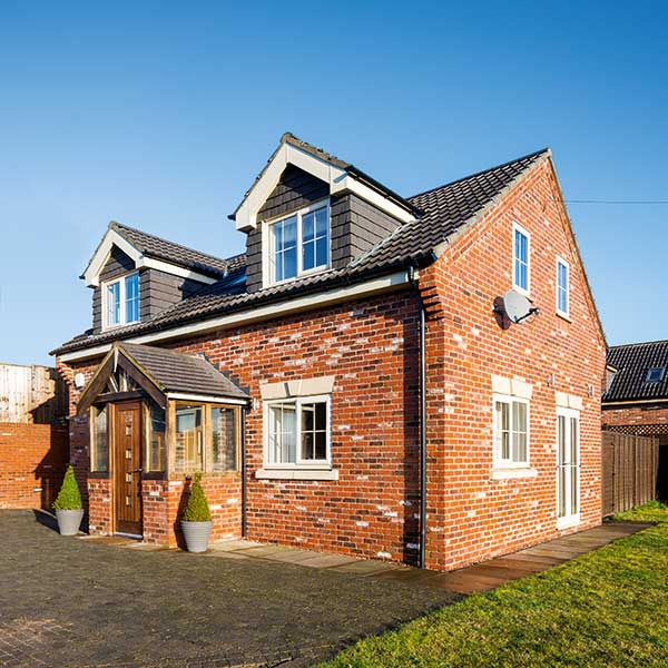 small red brick home self build with porch and dormer windows