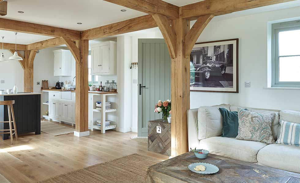 oak beamed living space with white and light green interiors