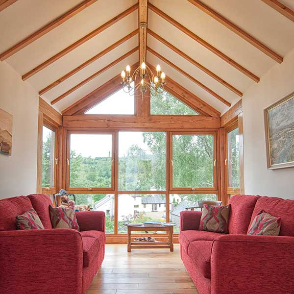 living room in self build with tiber beams and red settees and large wooden windows