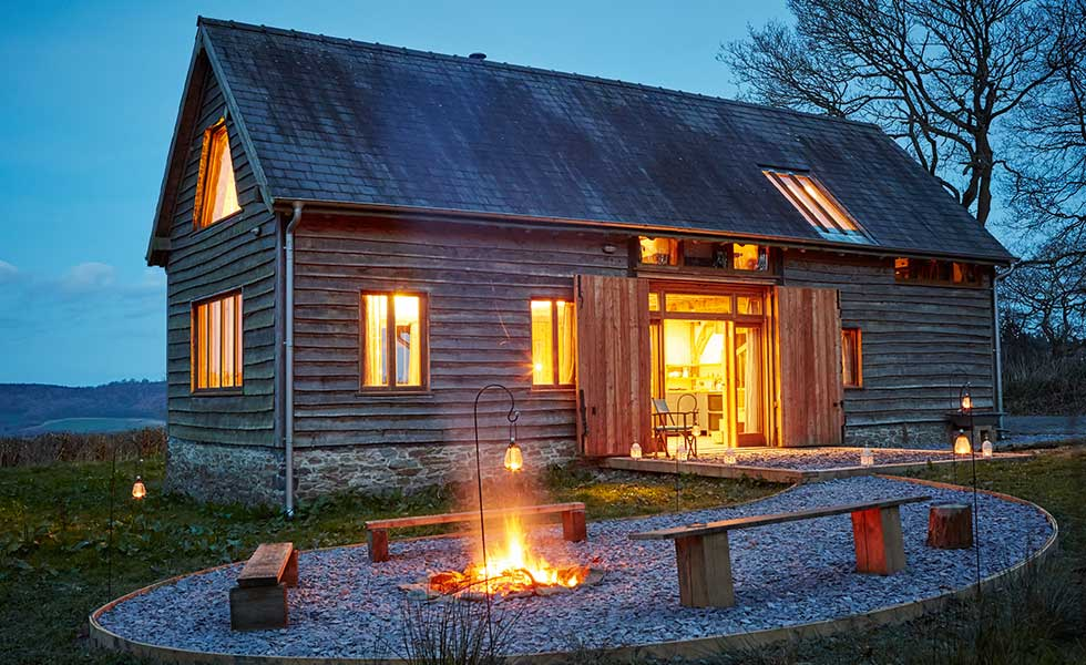 evening shot of self build barn with fir pit