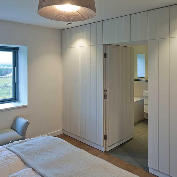 bedroom with cladding walls to bathroom