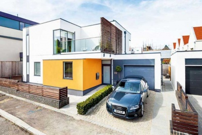 self build home as part of custom build project in Essex with white render and yellow ground floor