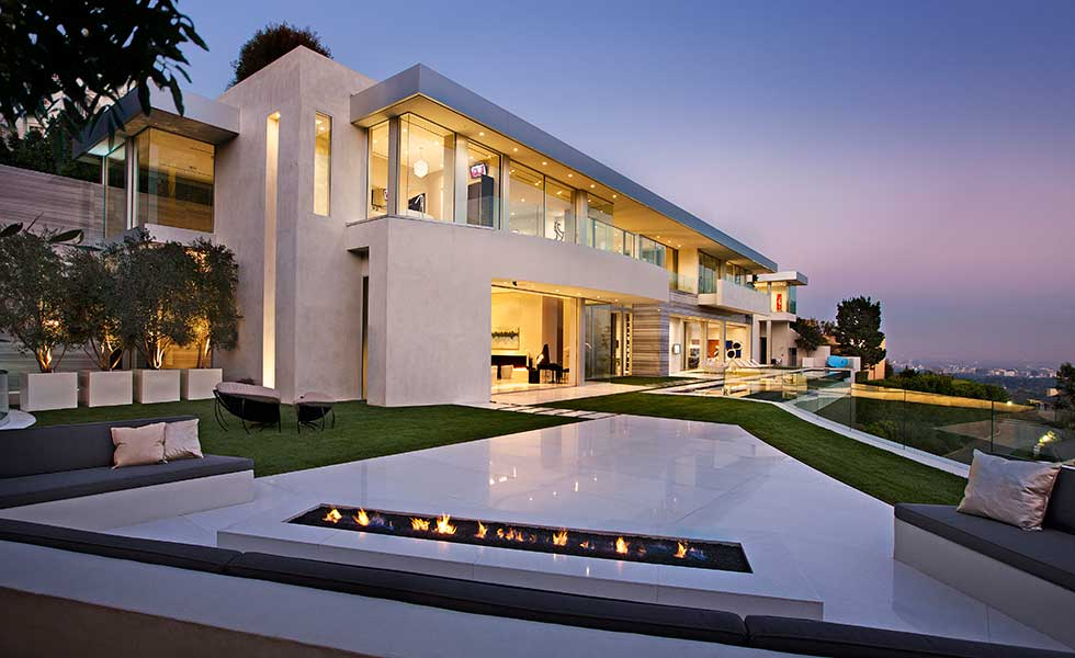 A fantastic Los Angeles home designed by McClean Design lit up at night over the city