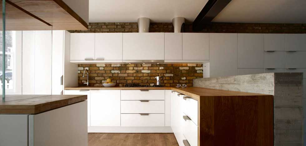 kitchen with exposed brick and white cabinets