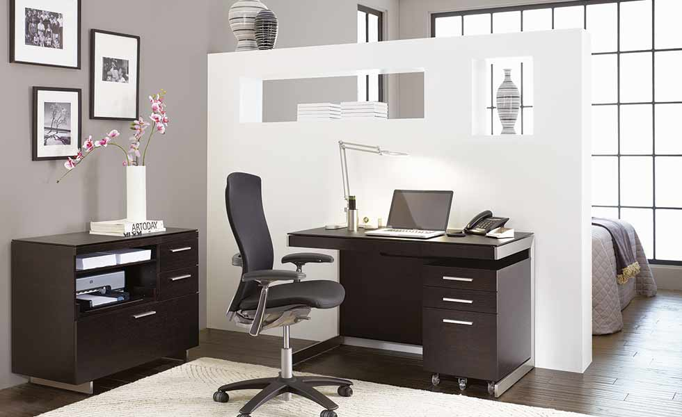 A room divide in this bedroom with desk to one side allows for this room to become a multifunctional space