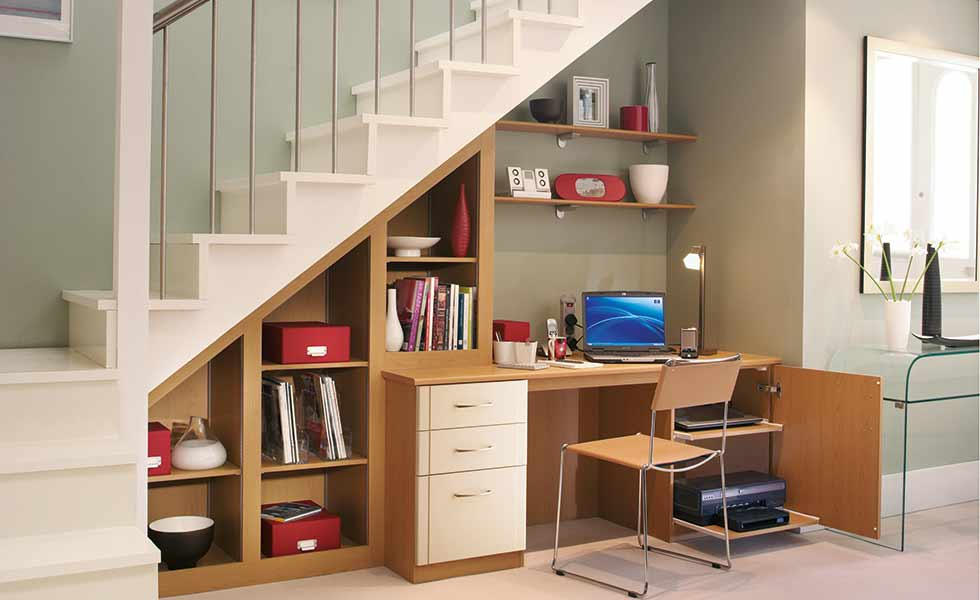 A desk with shelving under the stairs in this home is an ideal home office solution for those strapped for space