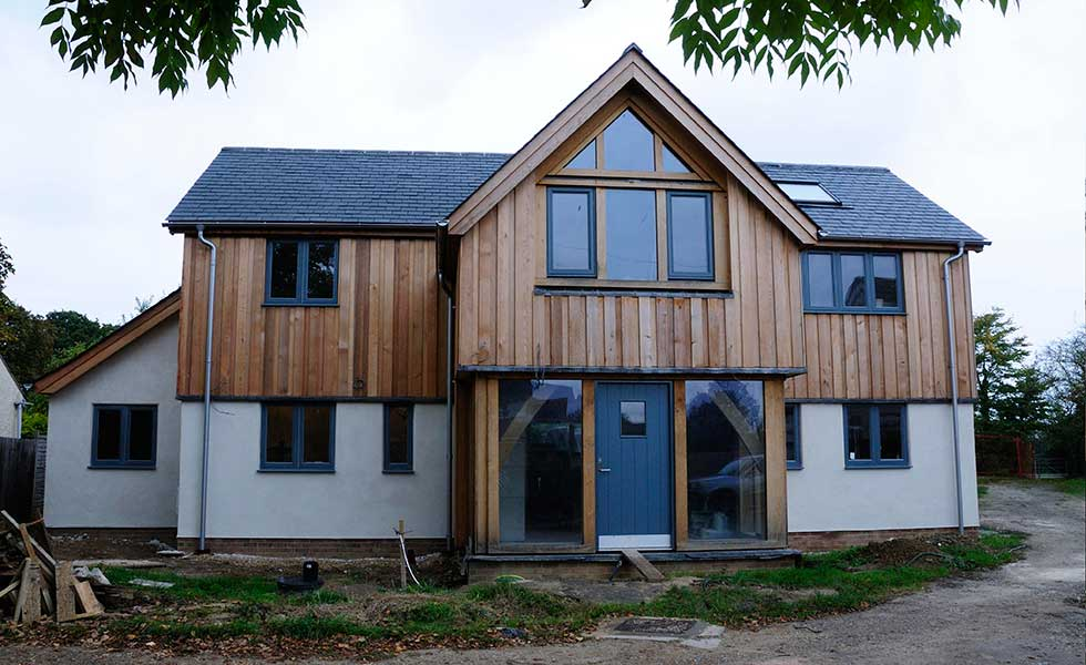 white rendered and timber clad oak frame and hempcrete home