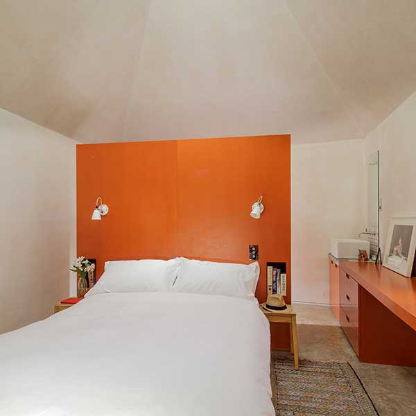 bedroom with orange furniture and white bedding