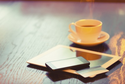Close-up of a credit card, mobile phone and digital tablet with a lens flare. The items are lying on a table, and there is cup of black coffee behind these items with steam. Online shopping concept. Copy space