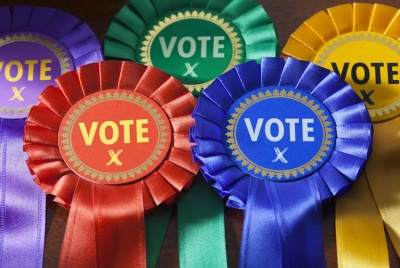 Voting in a UK Election. Coloured Rosettes for the principal UK political parties