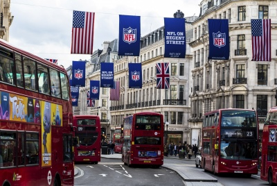 London, UK - October 15, 2016: Lots of iconic red London buses on the road in Regent Street, one of the most famous shopping streets in London. The streets are completely thronged with people, while above them the union jack flag of the UK, the American flag, and a banner with the NFL - National Football League - logo, recede into the distance.